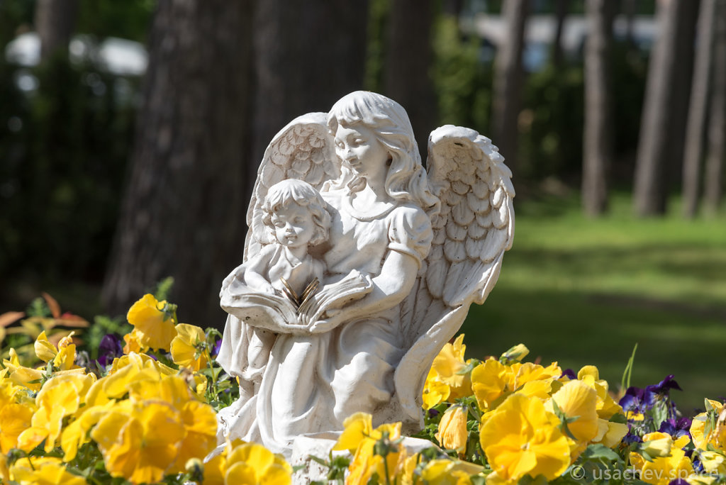 The figure of an angel with a child among the flowers in a flower bed near the Church of Our Lady of Kazan in Zelenogorsk.